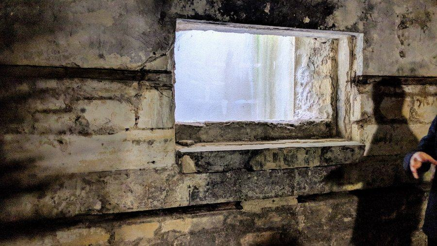 A concrete wall with a small window in it