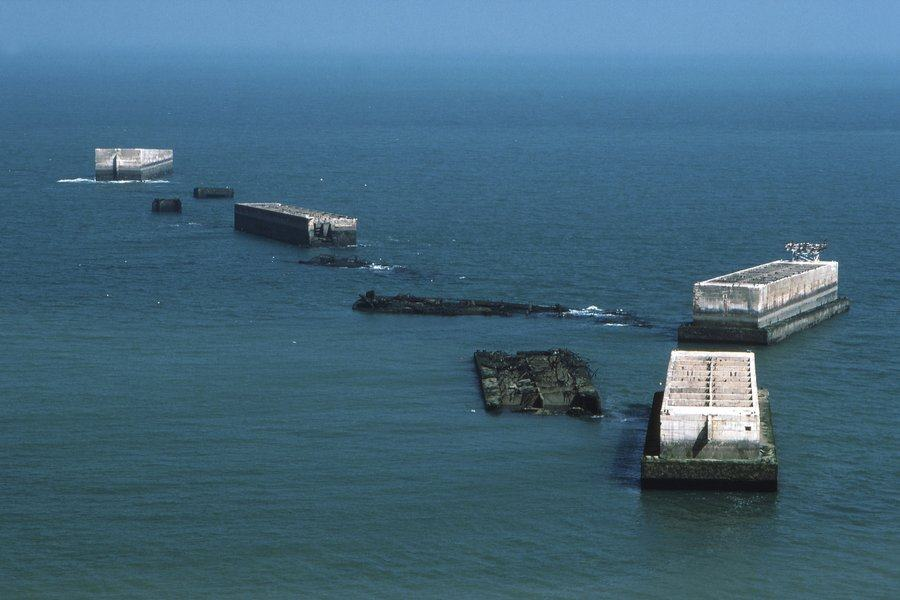 An aerial shot of a string of damaged concrete caissons in a blue sea