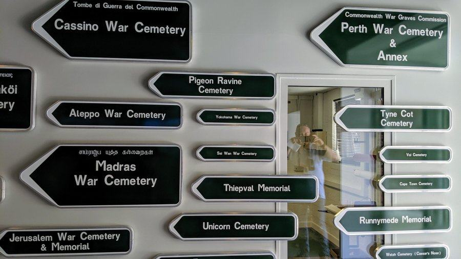 A wall covered with green directional signs with white writing