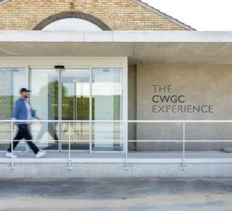 A man walks towards the glass door entrance of the Commonwealth War Graves Commission Experience