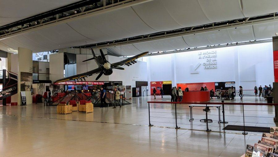 Large open space with a ticket office in the corner and a Typhoon aircraft suspended over it