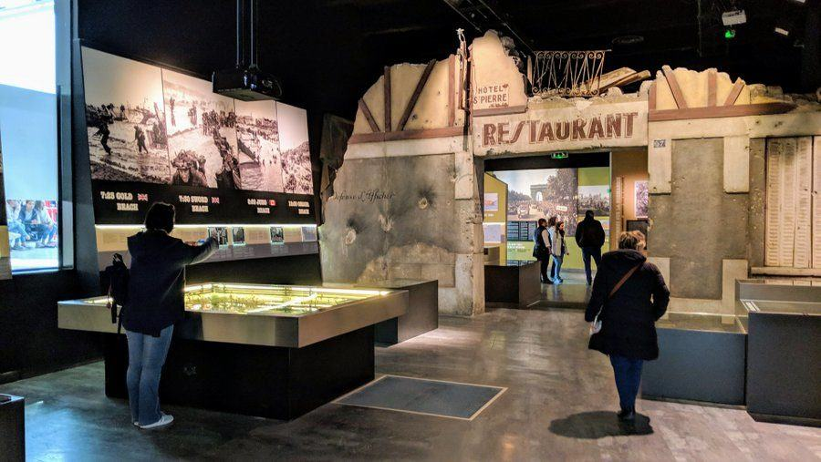 A room with recreated damaged Normandy buildings and table displays