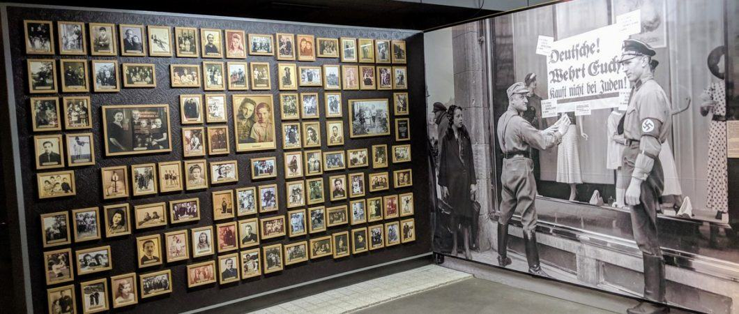 Wall display of framed pictures of jewish families juxtaposed with a full size b/w photo of german police marking a jewish shop window