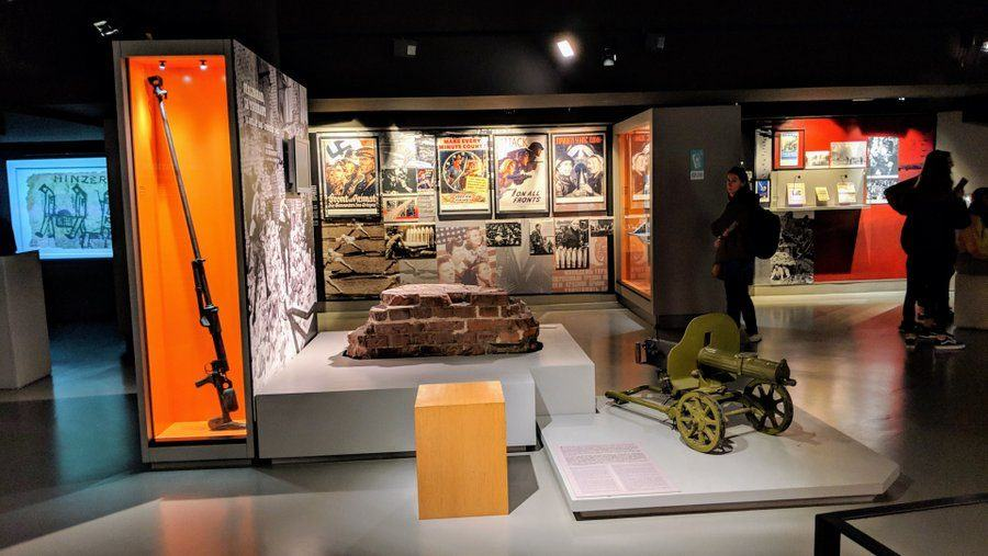 Museum gallery with old posters on the wall and guns on display