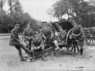 B/W image of six officers lounging on a field gun