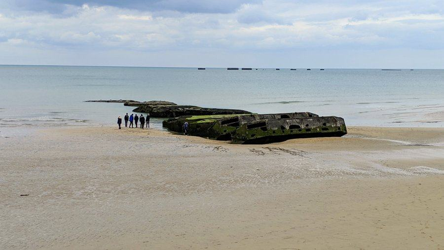 A small group of people walk by a pile of concrete pontoons on a beach