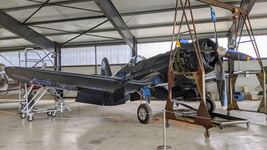 A dark blue, gull-winged Corsair with a lifting gantry poised over the engine, in the Salis Flying Museum