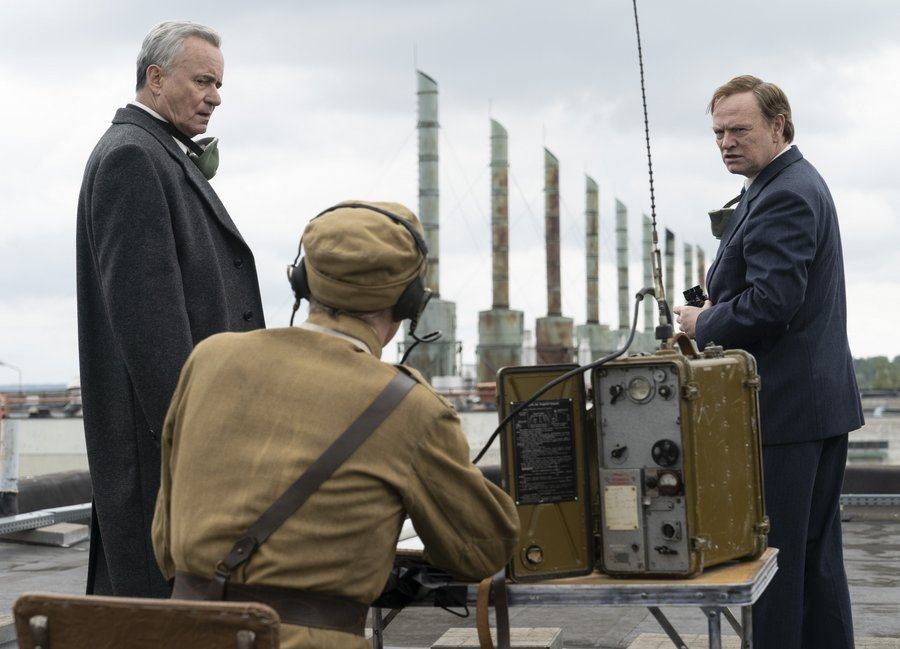 Two actors in suits on a rooftop consult with a soldier sitting at a table with an old fashioned radio set