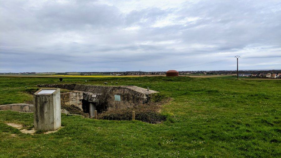 The sunken entrance way to a bunker buried in a field with the sea in the distance
