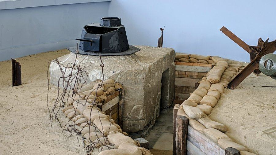 A trench with sandbags & barbed wire leads to a concrete bunker with a tank turret on top
