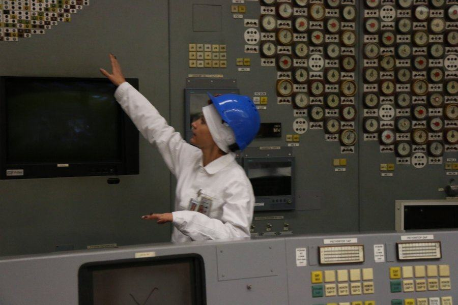 A woman worker in white suit and blue helmet points to something on the control room wall
