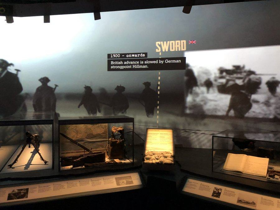 A dark gallery with D-Day artifacts and a photographic timeline above on the wall