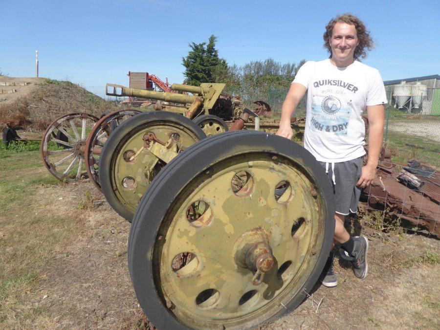 Daniel Sterne in a white t-shirt standing by a field gun axle & wheels