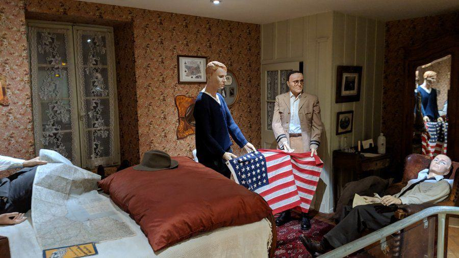 Mannequins of the crew in a bedroom holding a Stars & Stripes flag