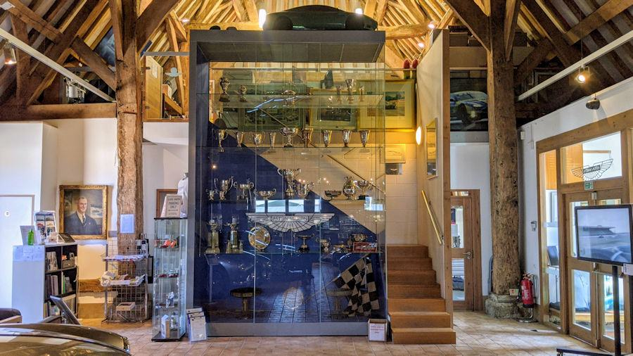 A glass cabinet with Aston Martin Racing cups & trophies