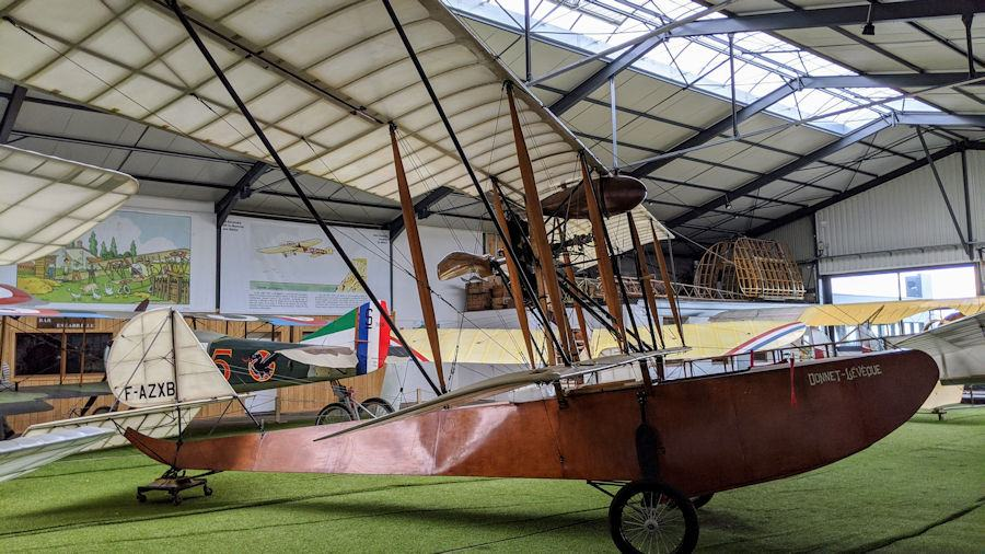 Small flying boat looking like a wooden canoe with an engine and wing supported on top. On display at the Salis Flying Museum