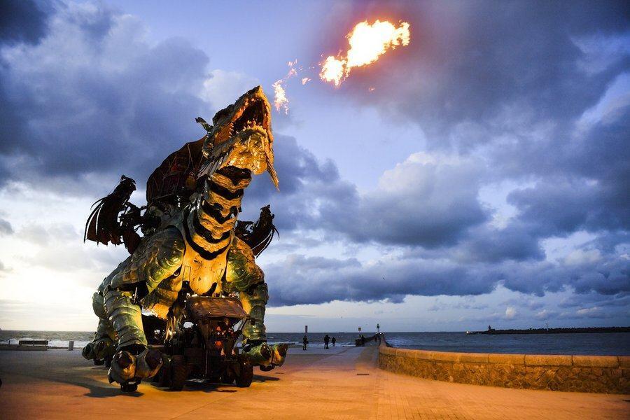The dragon blast flames skyward against darkening skies