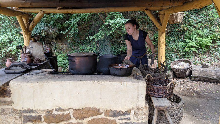 A woman heats large pots on a stove