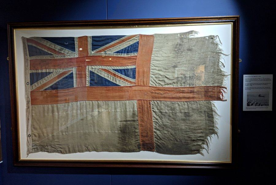 A battle scarred White Ensign flag displayed in a frame on a wall