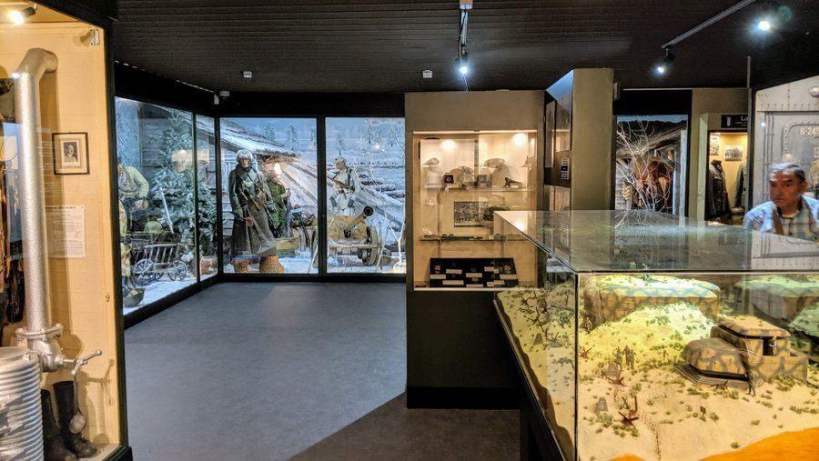 A gallery with a model of Atlantic Wall bunkers in the foreground and a winter war diorama in the distance