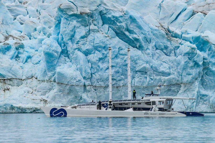 Energy Observer close to a blue & white glacier