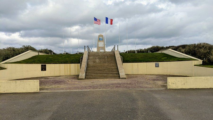A memorial with steps to a plinth and national flags