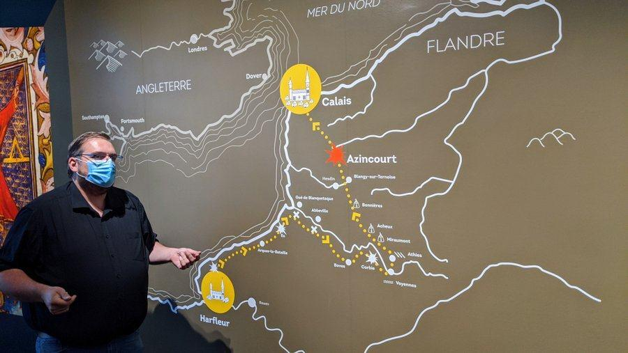 Christophe Gillot in a facemask stands by a wall map