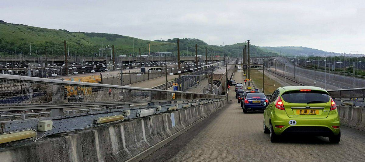 A line of cars driving down the ramp to a Eurotunnel Shuttle train