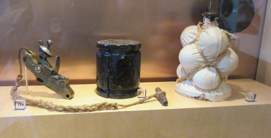 Items in a display of early 19th century ordnance including a bulging white sack of small shot