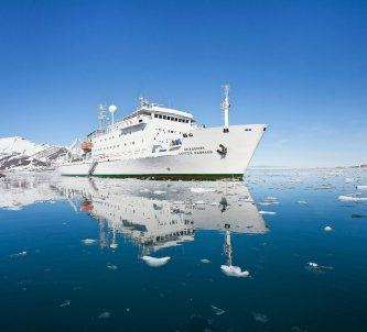 White hulled expedition ship on a dead calm sea surrounded by icebergs