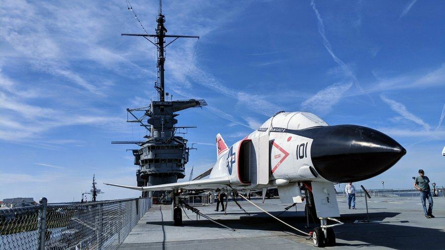 Classic Vietnam era jet fighter with a black nose sits on the flight deck with USS Yorktown's island behind