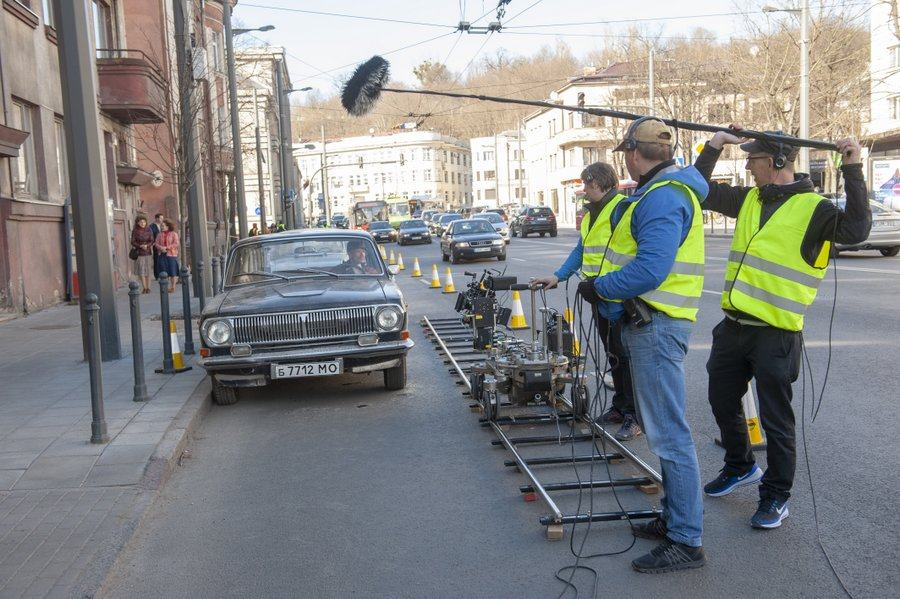 A film crew with a camera dolly track and boom mic, film an actor in a classic car parked at the side of the street