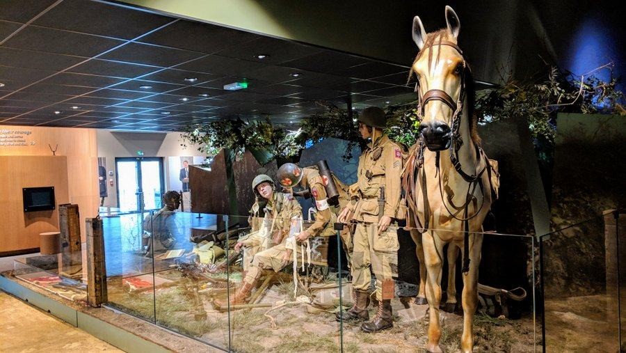 A diorama. A paratrooper is bandaged up by a medic while another soldier, holding a horse's reins, watches.