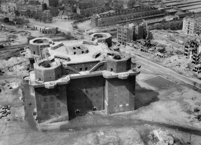 Black & white aerial photo of the castle-like flak tower in 1945, surrounded by the bomb damaged buildings of the St. Pauli district of Hamburg