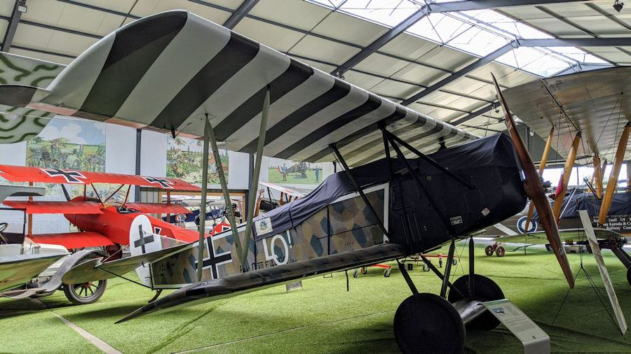 Green painted German biplane with b/w stripes on the undersides of the wings. The Fokker DVII is displayed in a hanger at the Salis Flying Museum