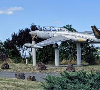 A silver jet aircraft with V-shaped tailplanes sits on three white concrete pillars