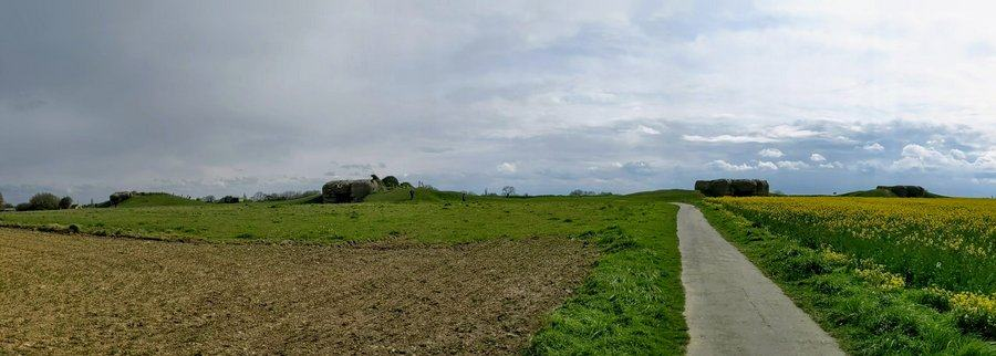 Panorama of ploughed field with four gun emplacements on the horizon