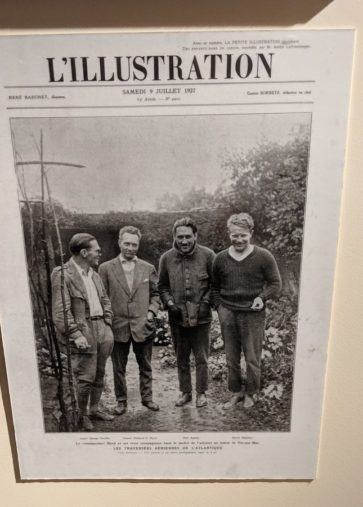 The front cover of a newspaper with a large black & white photo of the four crew members of 'America' standing in a garden