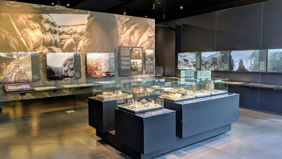 A museum gallery with display cases and images on the walls