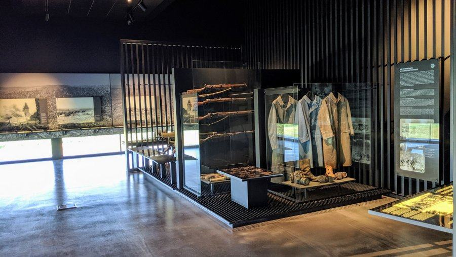 A museum gallery with uniforms and machine guns on display