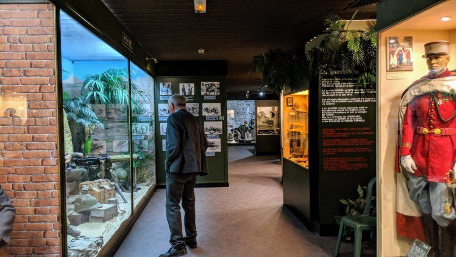 A man looks at a WW2 diorama behind a glass wall