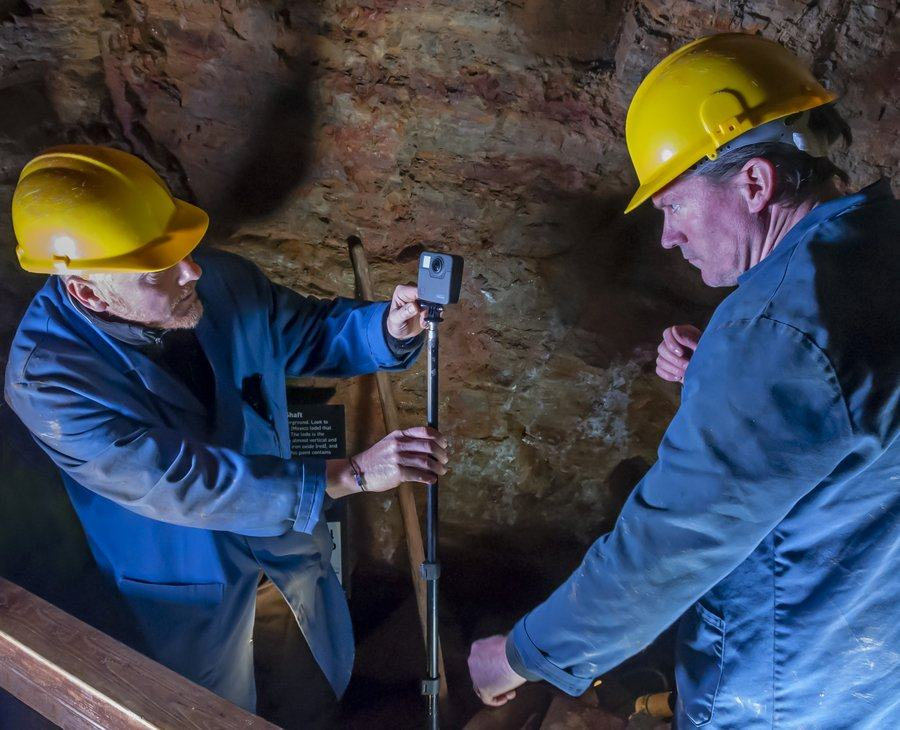 Two men in blue overalls & yellow hard hats set up video equipment in a mine tunnel