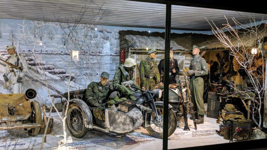 Soldiers in a winter setting with a motorcycle & sidecar in the foreground