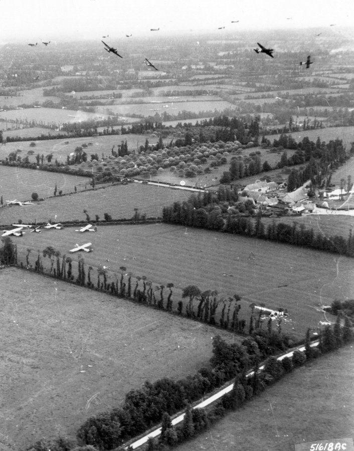 Black & white photo of gliders & tow planes circling over their landing zone, with some gliders already on the ground