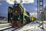 A steam loco belches out smoke in a snowy railyard.
