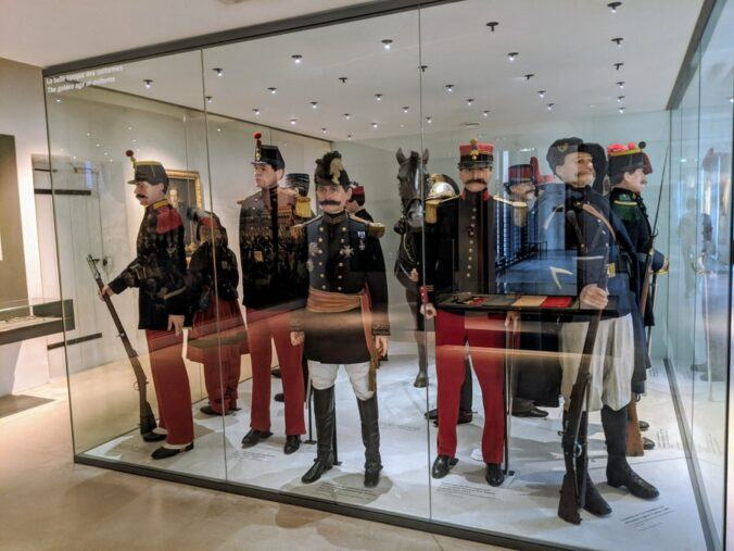 A glass display with a dozen uniformed mannequins