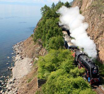 Luxury train with steam engine passing a lake