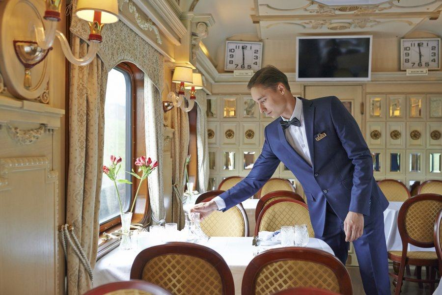A waiter lights a candle in the railcar dining room