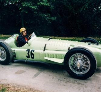 Driver with leather cap sits in a light green 1950s BRM Formula 1 race car