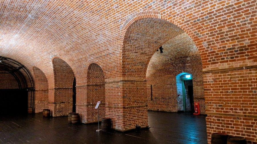 A large space with vaulted brick walls and ceiling